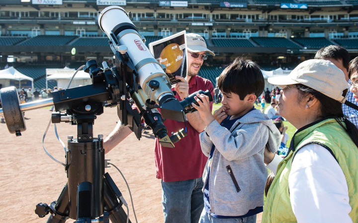 A curious young future scientist explores astronomy and telescopes at the Bay Area Science Festival. Credit: John van Eyck.