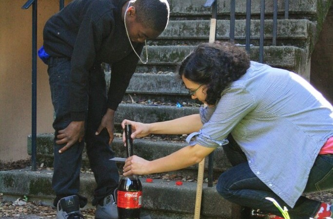 A student and mentor take their research on Coca-Cola geysers outside.